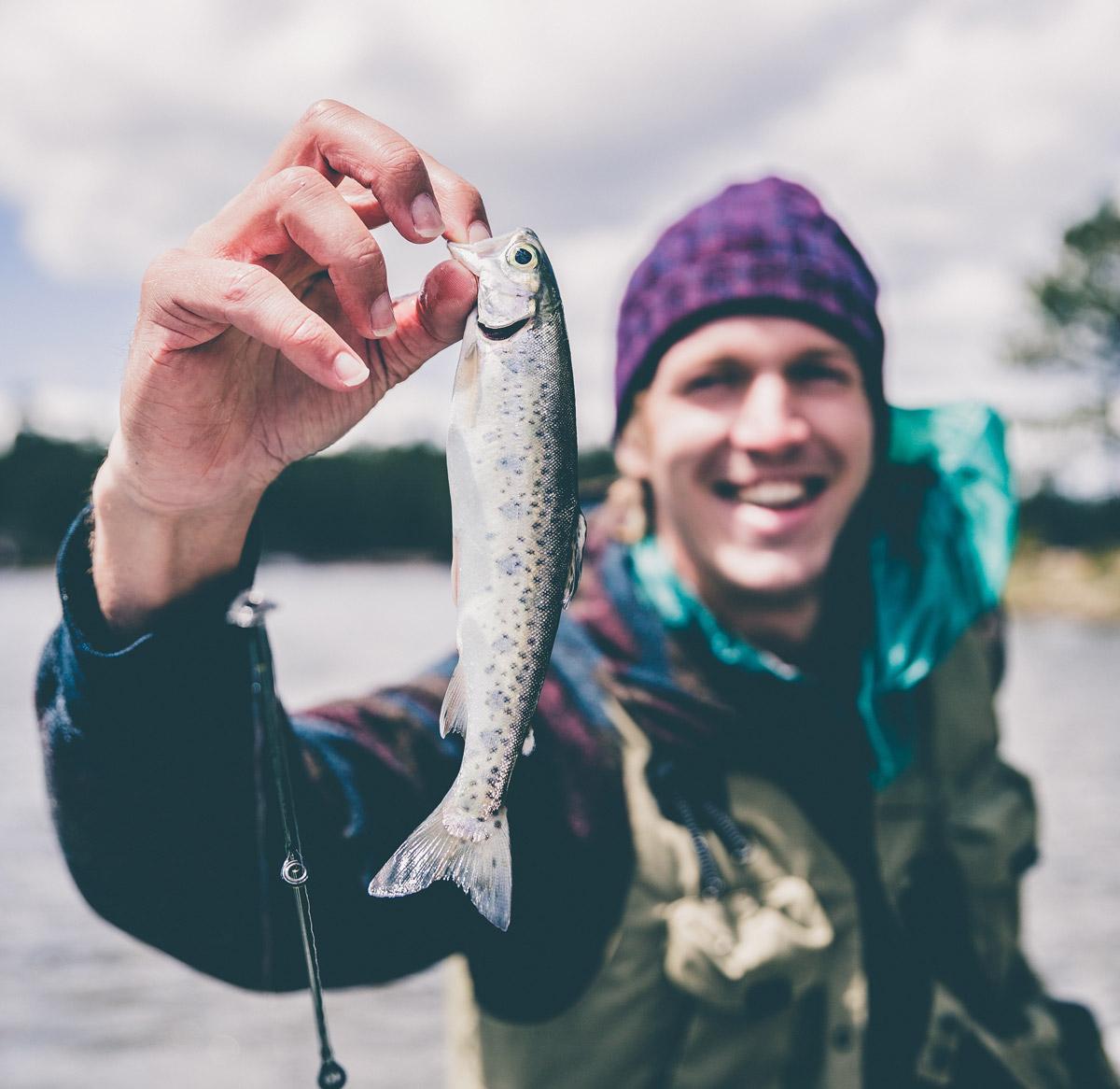 Homme qui tient un poisson - Appâts du nord